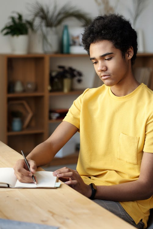 Man in Yellow Crew Neck T-shirt Writing on White Paper