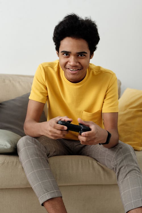 Boy in Yellow Crew Neck T-shirt and Gray Pants Sitting on Couch While Holding Remote Controller