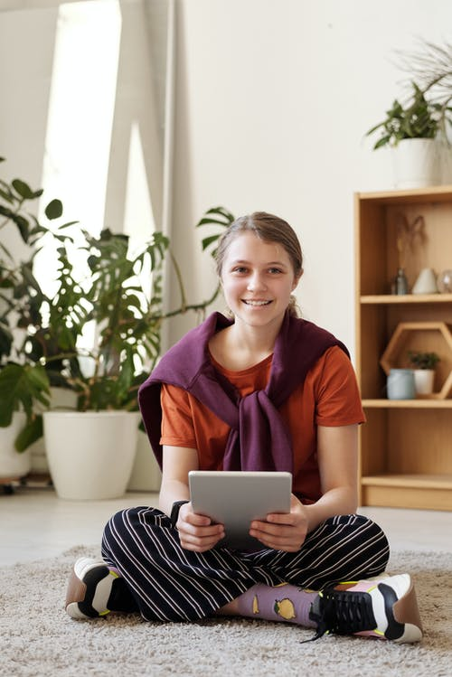 Girl Smiling While Holding Silver Ipad