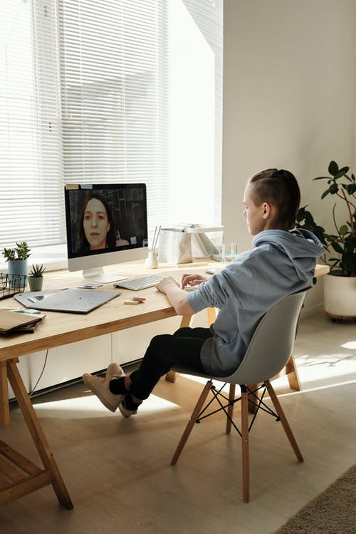 Photo of Boy Sitting on Chair While Looking at the Imac