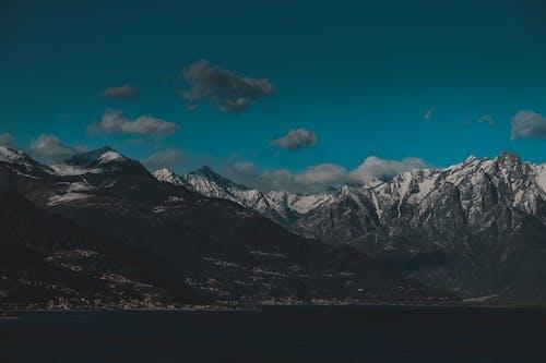 Snowy mountain peaks under blue cloudy sky