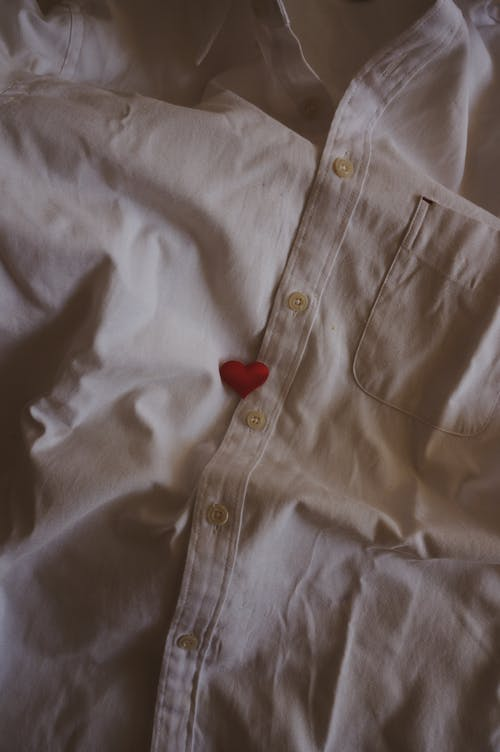 Top view of red heart placed on white cotton shirt with buttons at home