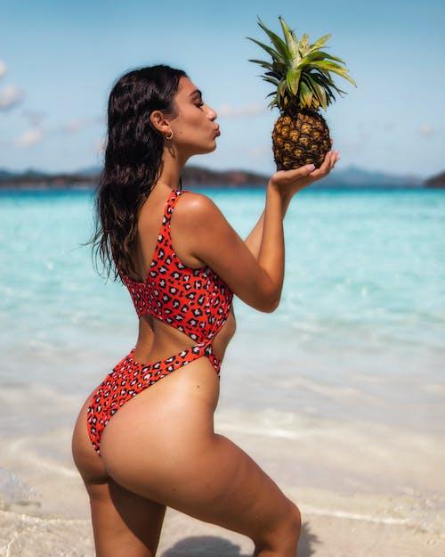 Woman in Red and White Polka Dot Bikini Holding Pineapple on Beach
