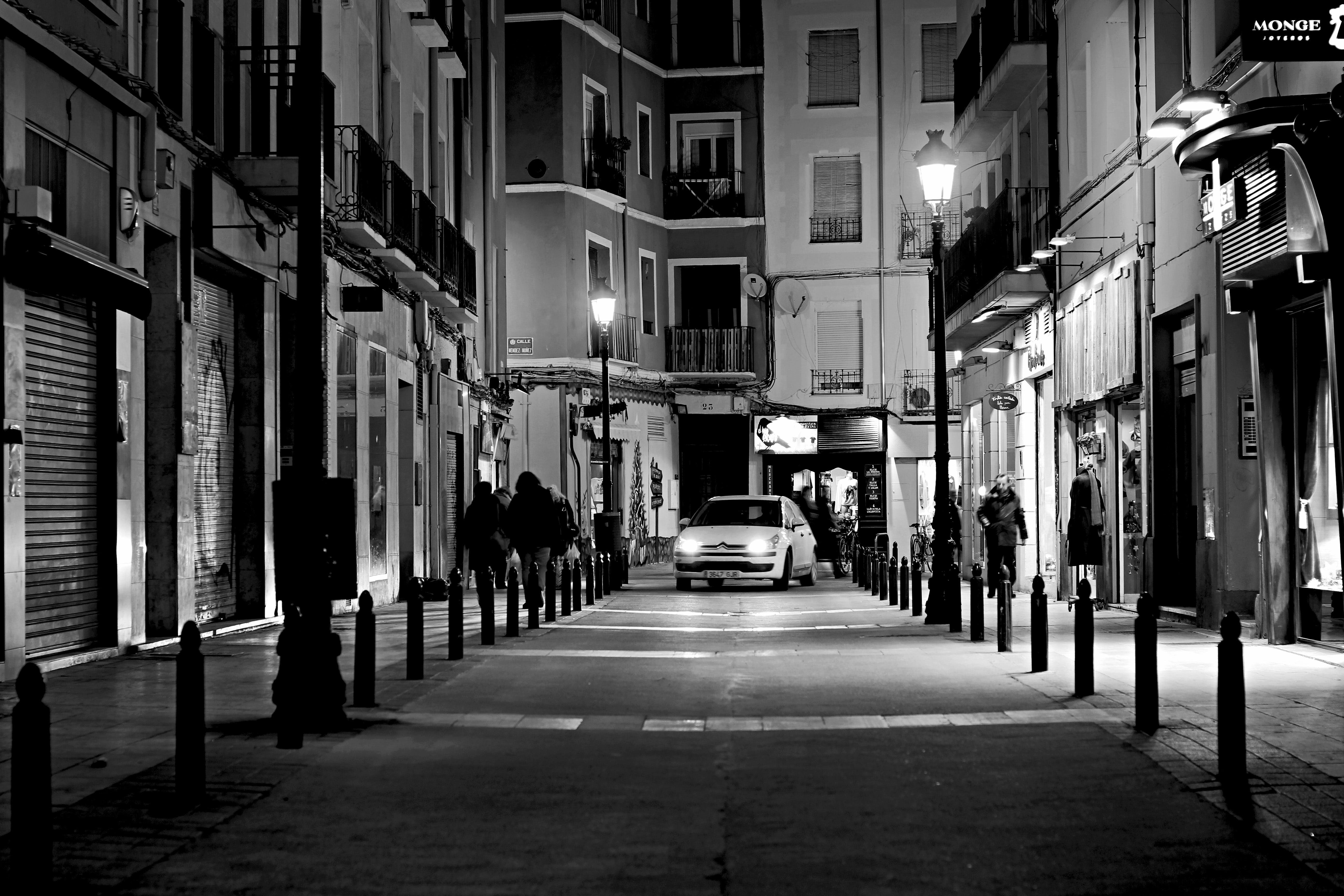 Grayscale Photography of Road Between Buildings