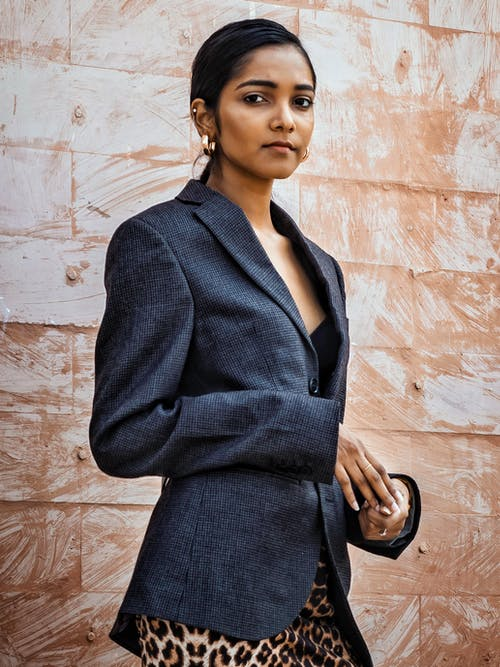 Serious ethnic female wearing classy jacket and dress looking away while standing against beige wall