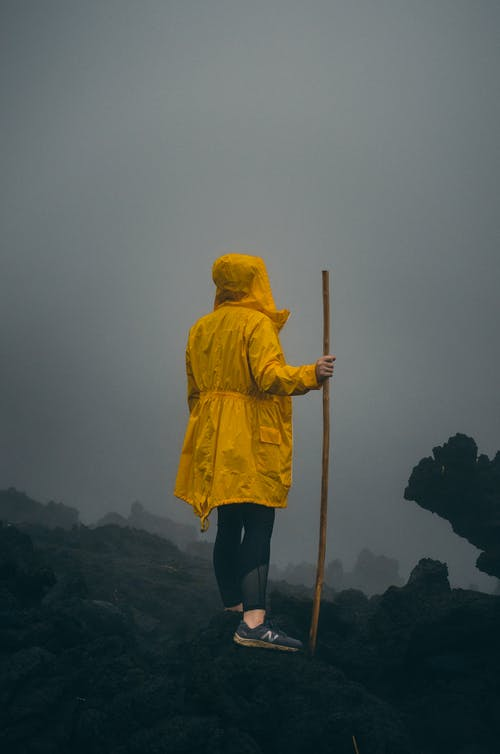 Person in Yellow Hoodie Standing on Rock