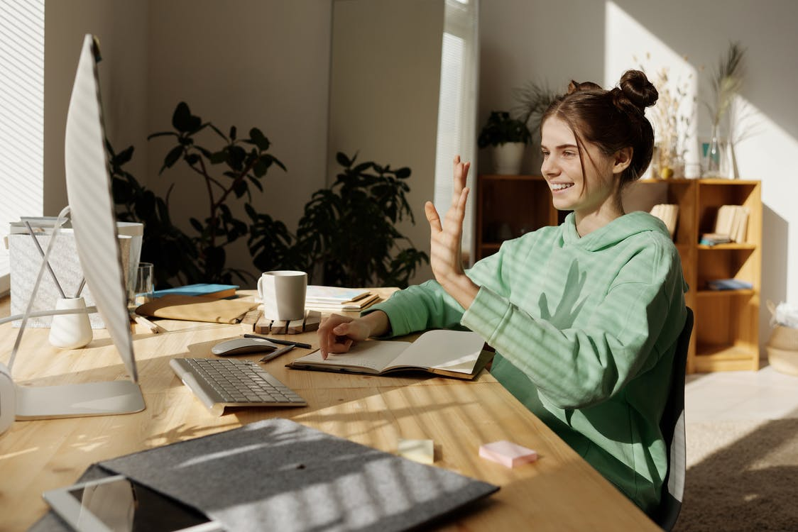 Woman in Green Shirt Sitting at the Table