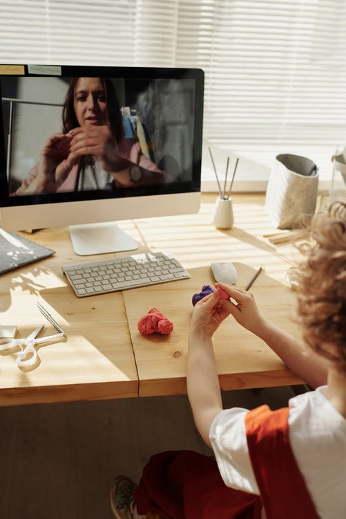 Photo Of Kid Playing With Clay While Looking In The Monitor