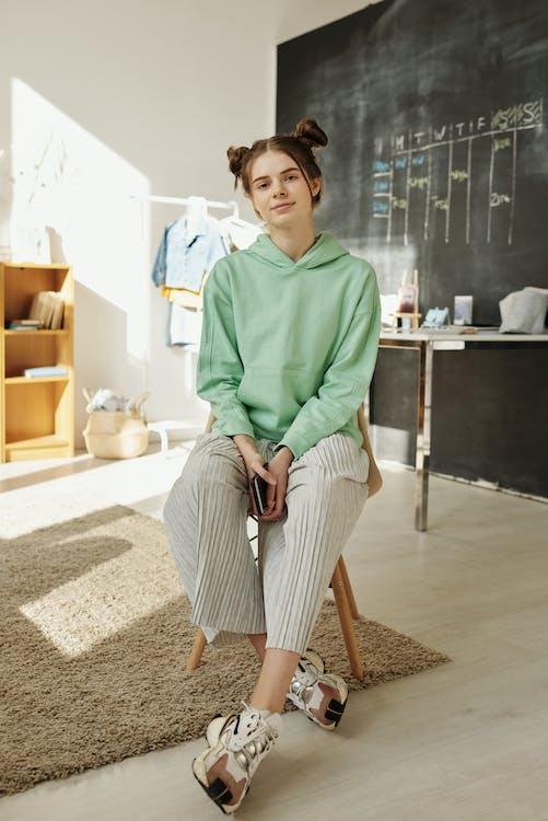 Girl in Green Hoodie Sitting on Chair