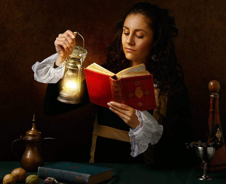 Focused woman in old outfit reading book with oil lamp