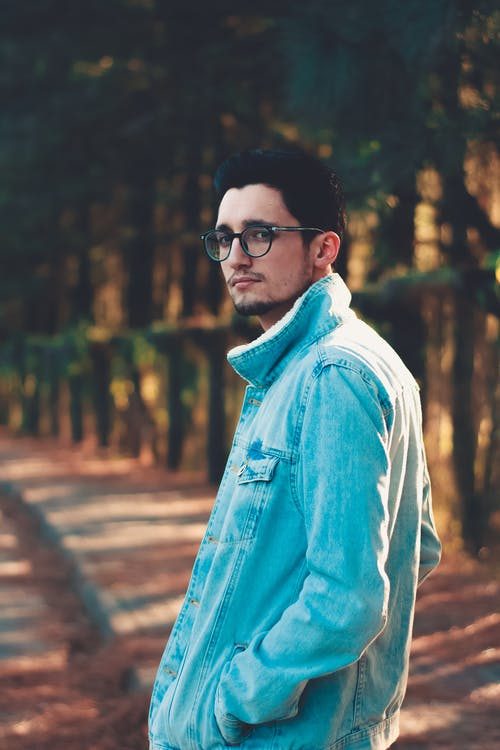 Side view of young man in denim jacket and eyeglasses standing in park