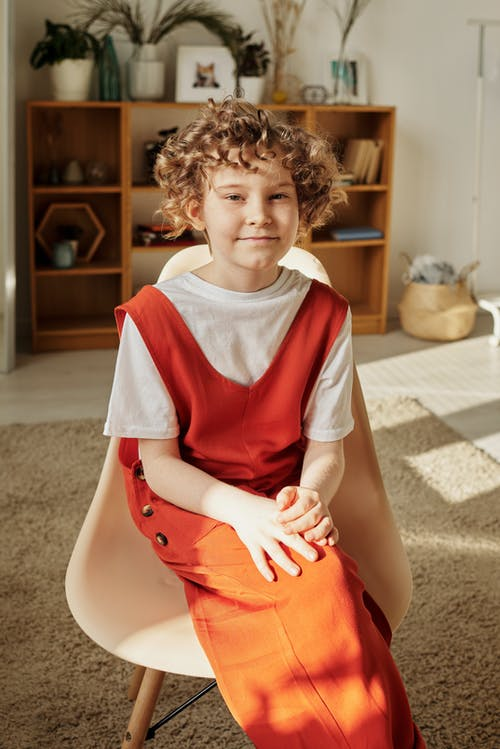 Boy in Red and White Dress Sitting on White Chair