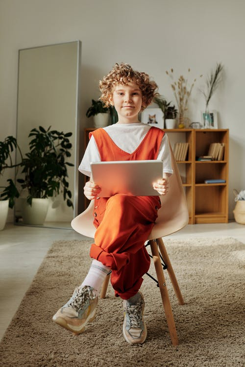 Photo of Child Sitting on Chair While Using Tablet