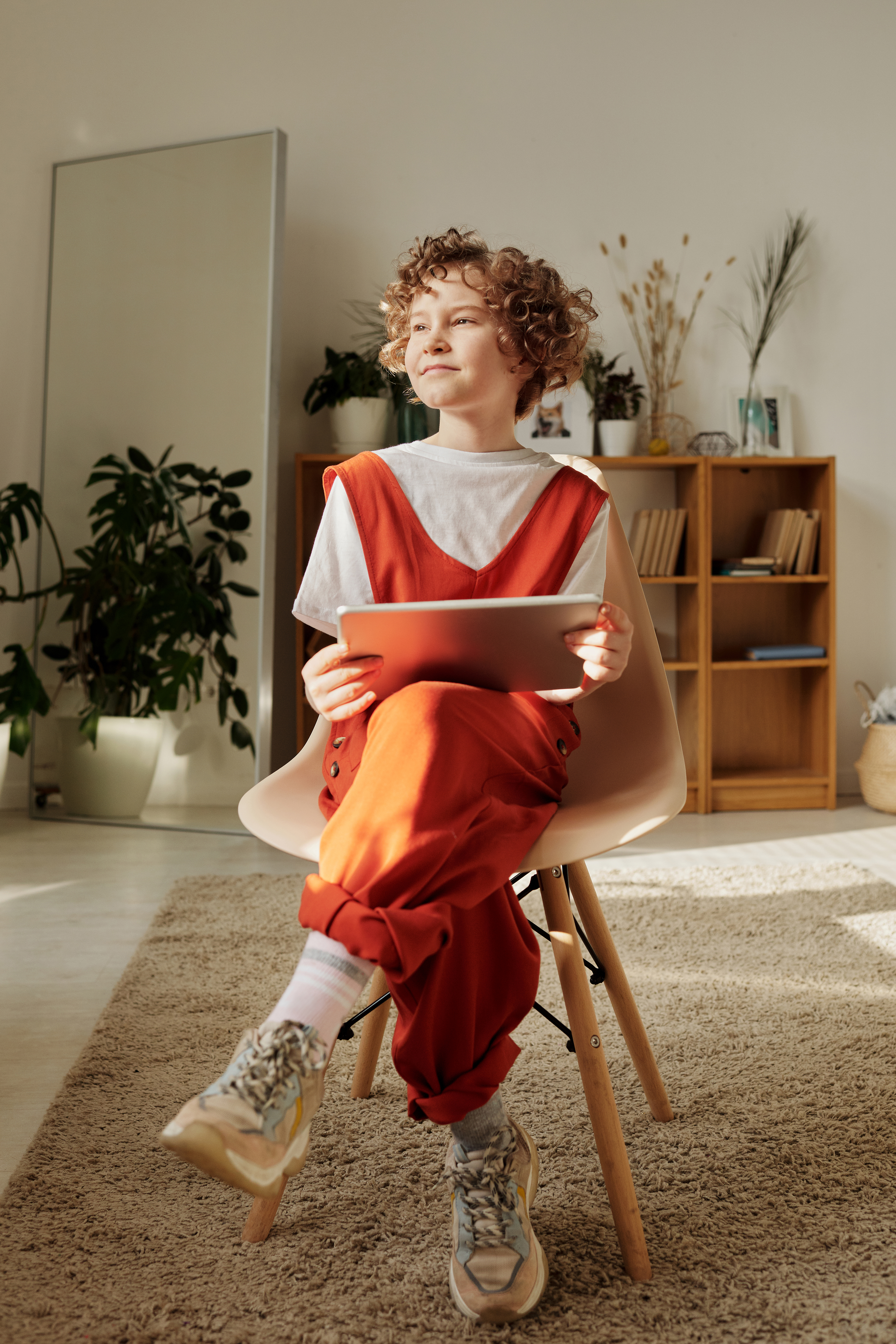 photo of child sitting on chair while holding tablet