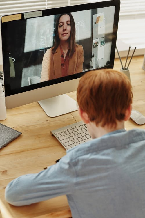 Photo of Boy in Blue Dress Shirt While Video Calling With a Woman Through Imac