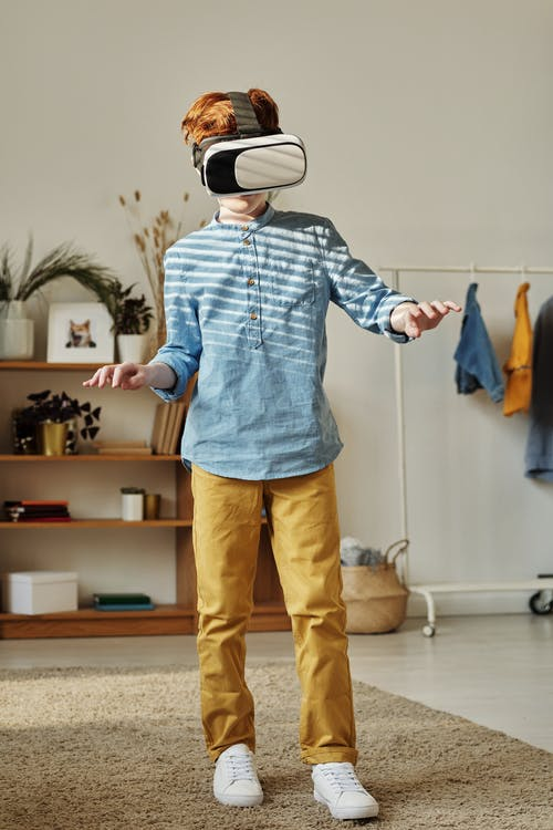 Boy in Blue Dress Shirt and Brown Pants While Using Vr Headset