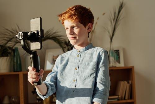 Boy in Blue Dress Shirt Holding Black Selfie Stick