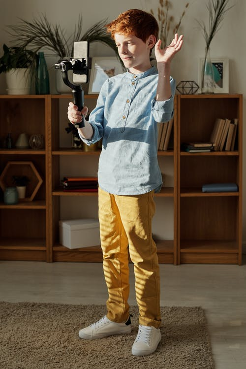 Photo of Boy Standing While Holding Black Selfie Stick