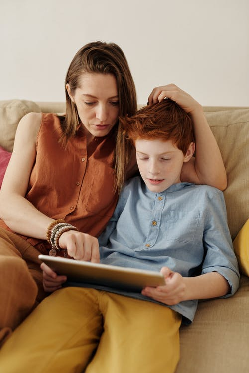 Photo of Woman and Boy Sitting on Couch While Using Tablet Computer