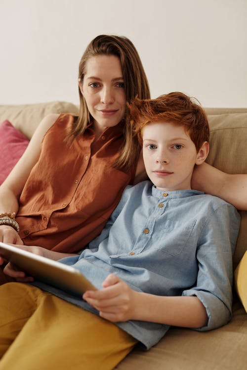 Photo of Woman and Boy Sitting on Couch