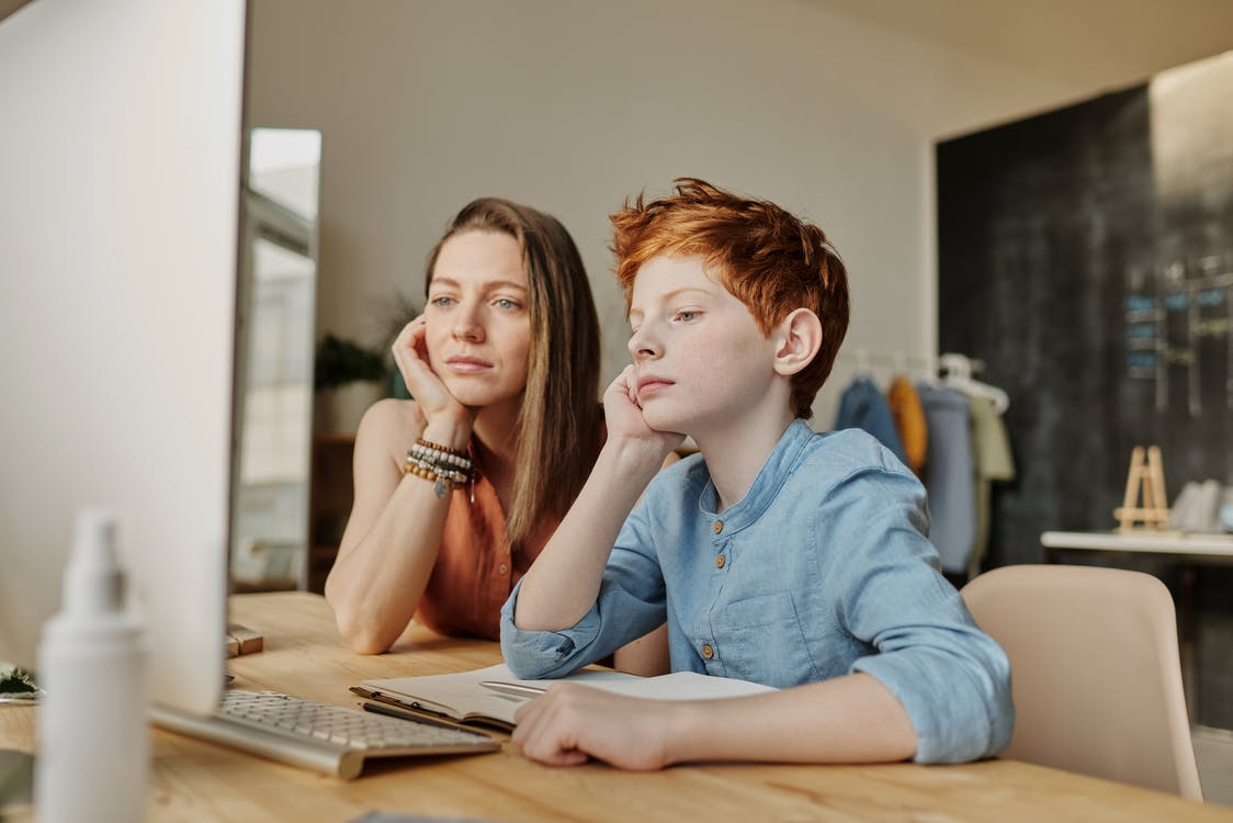 Photo of Woman and Boy Leaning on Wooden Table
