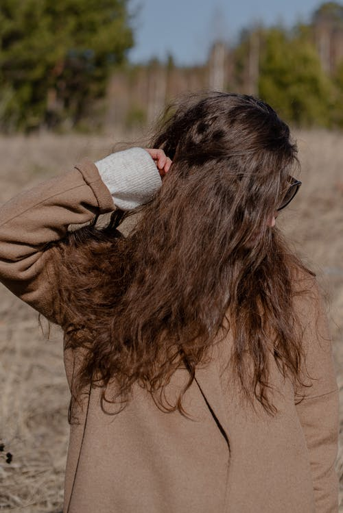 Young woman in warm clothes in field