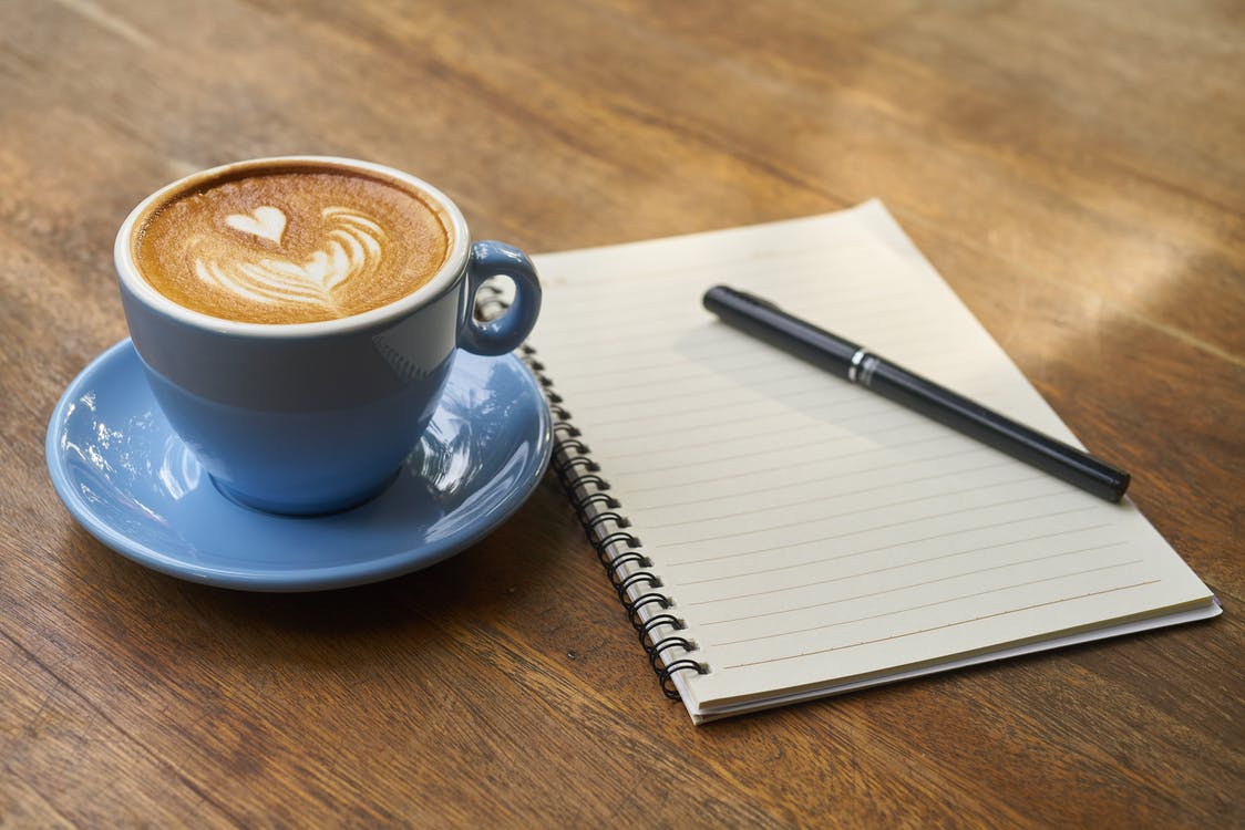 Coffee on Saucer Beside the Notebook
