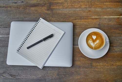 Teacup of Latte on Saucer Beside Notebook