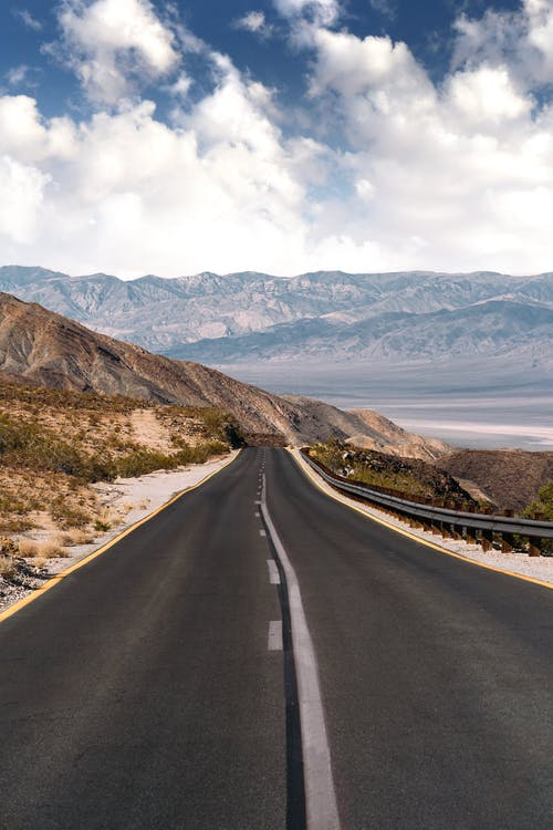Asphalt road through mountainous terrain in overcast weather