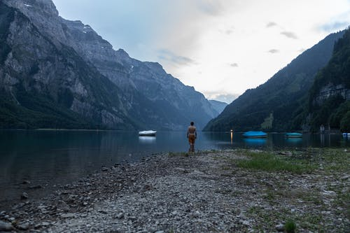 Person in Red Shirt Standing Near Lake