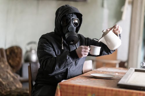 Person in Black Leather Jacket Wearing Black Gas Mask