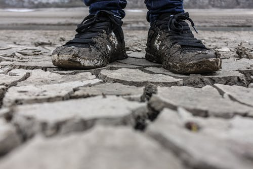 Person Wearing Black Hiking Boots Standing on Gray Concrete Pavement