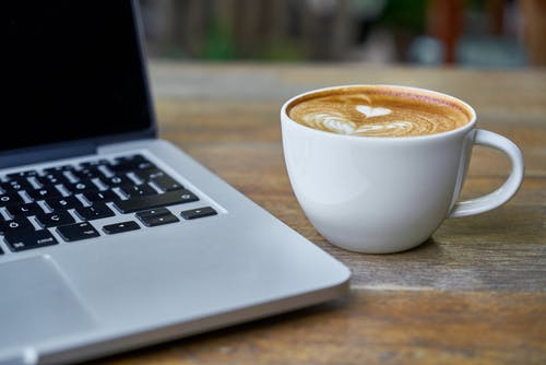 Teacup of Latte Beside Macbook Pro