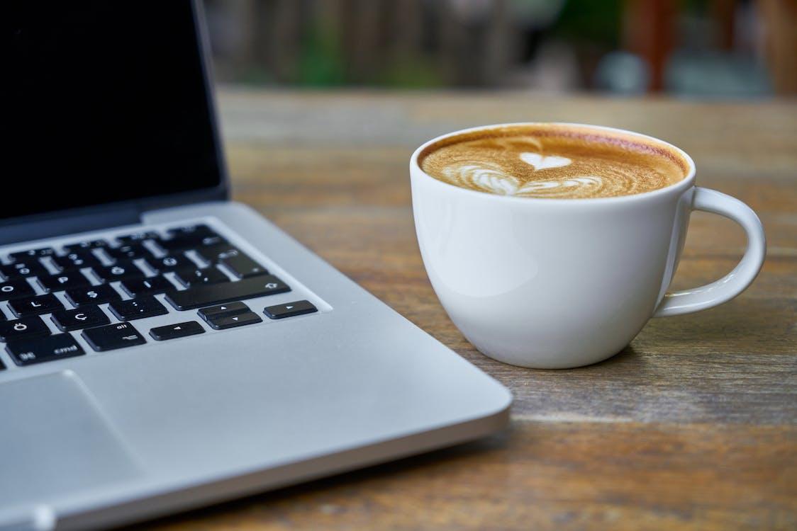 Teacup of Latte Beside Macbook Pro