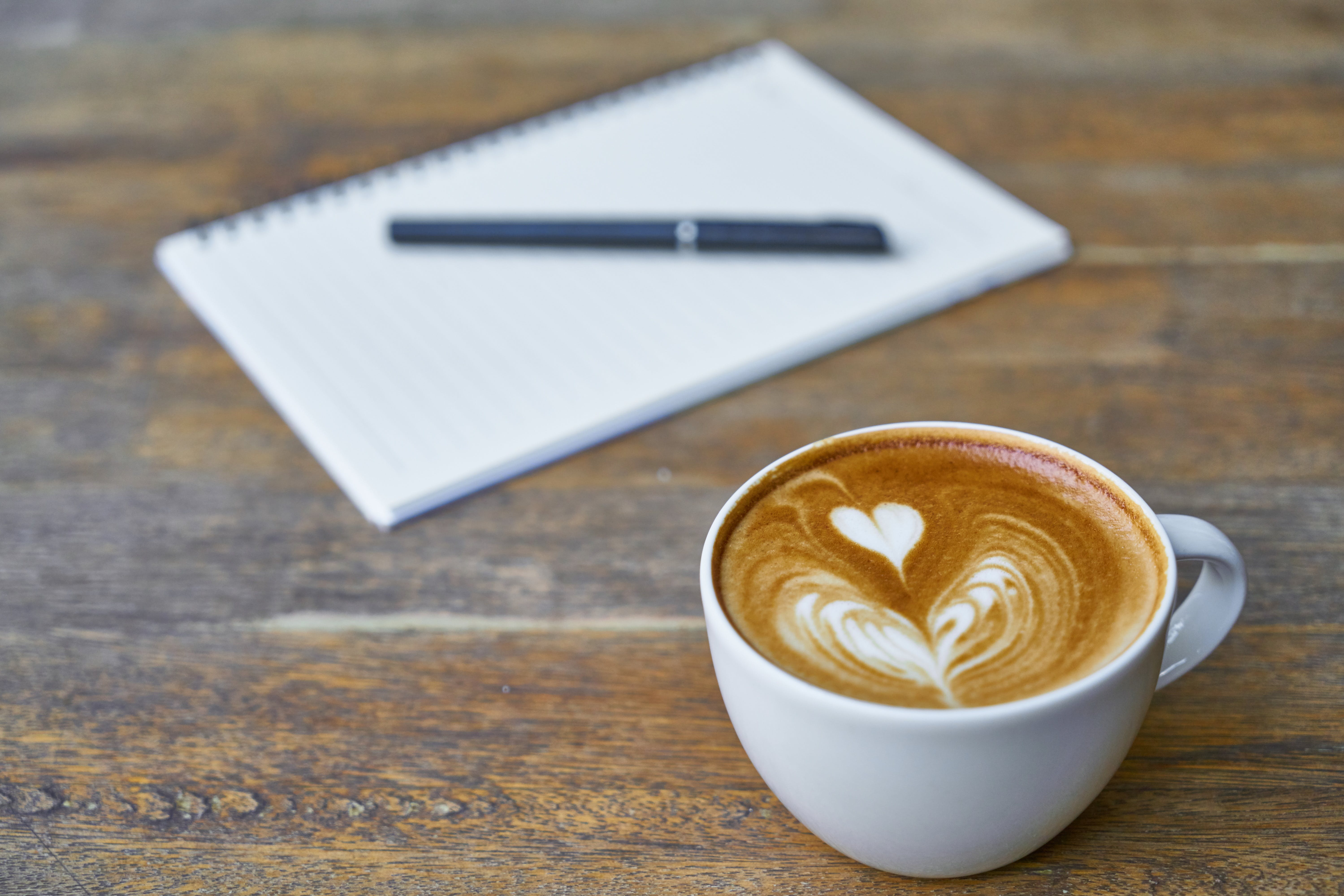 Ceramic Cup Filled With Coffee Beside Notebook and Ballpoint Pen