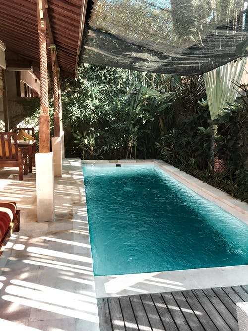 Terrace of resort villa with swimming pool surrounded by tropical green trees on sunny day