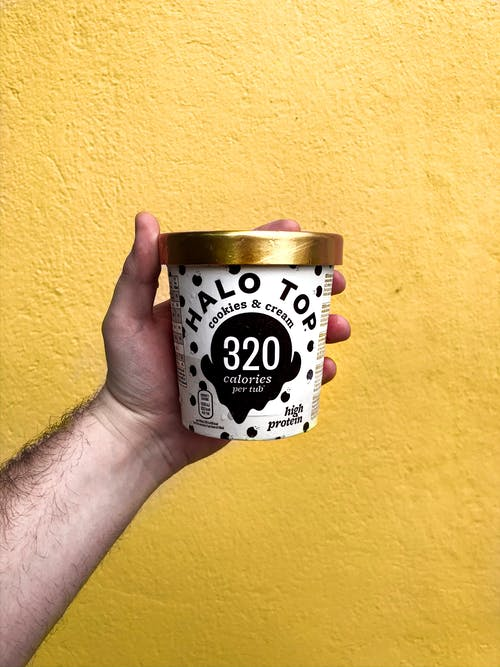 Hand of unrecognizable male with low calorie high protein ice cream on yellow  background