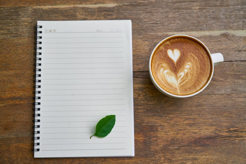 Cappuccino Coffee Beside the Notebook