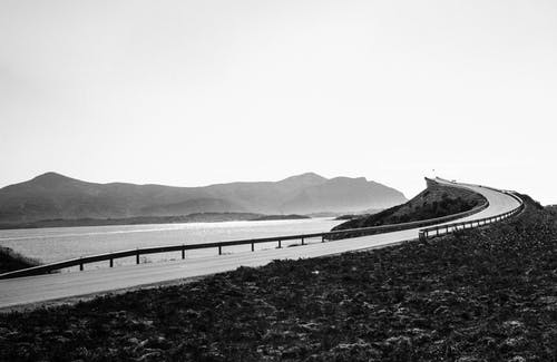 Black and white asphalt roadway going along calm sea and hills on shore