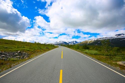 Asphalt road towards mountainous terrain through green valley