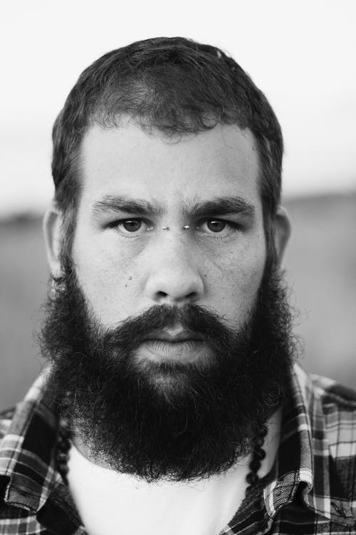 Grayscale Photo of Man in Plaid Shirt