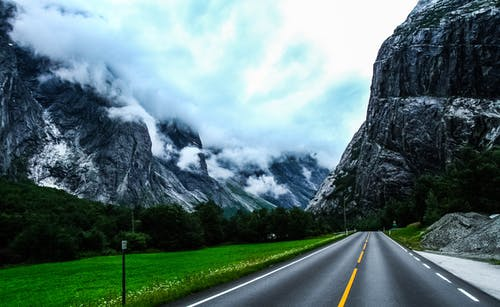 Straight roadway among mountains under clouds