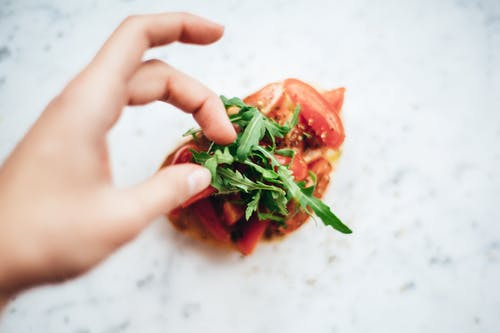Person Holding Green and Red Vegetable