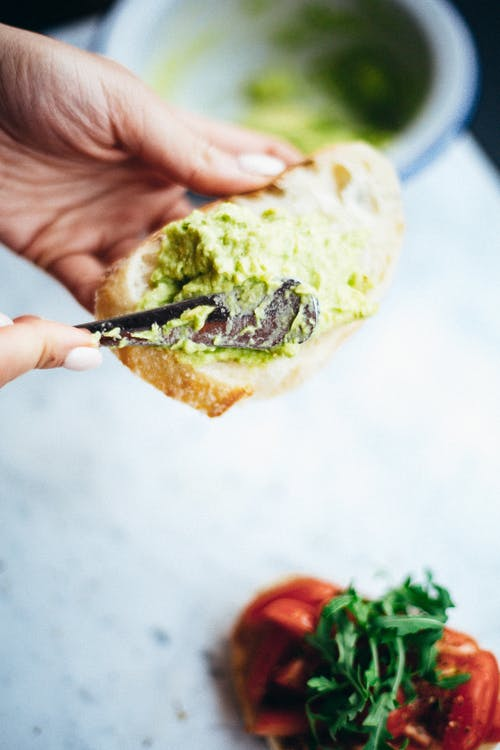 Person Holding Bread With Green Vegetable
