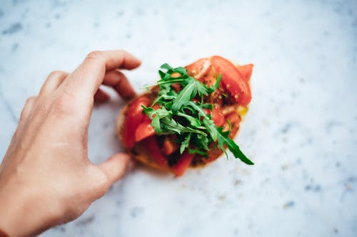 Person Holding Sliced Tomato and Green Vegetable