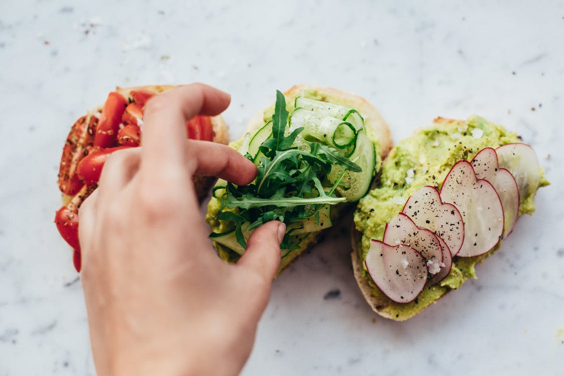 From above of crop anonymous person adding arugula on bruschetta with cucumber and avocado placed near slices of bread with tomatoes and radish