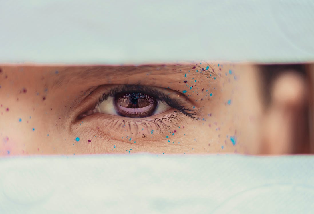 Crop woman brown eye with drops of paint on face