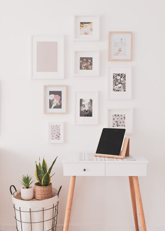 Interior of modern light bedroom with cozy white vanity table with contemporary tablet with black screen on creative stand near potted houseplants