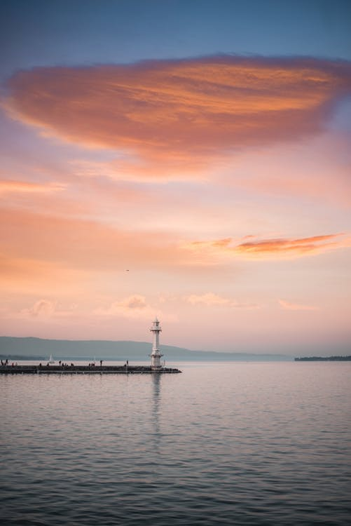 Lonesome lighthouse on pier near sea in sunset light