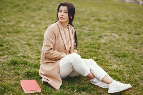Full body thoughtful dark haired female in casual outfit in light colours sitting on lawn with book and looking away